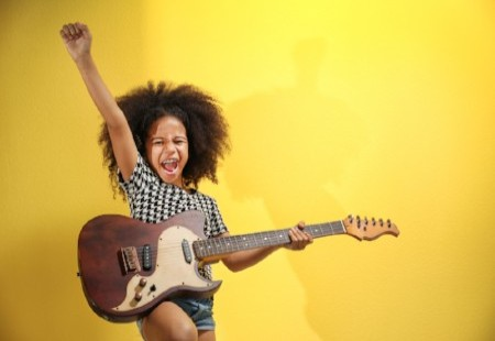 girl playing guitar like a rock star