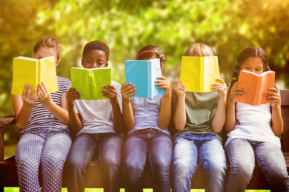 Children reading books outdoors